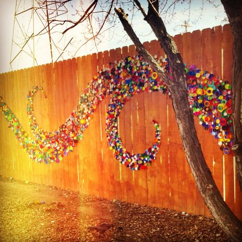 Make your fence more interesting with colorful bottle caps and an artistic touch
