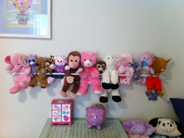 Use a metallic bar attached to the wall to securely hold stuffed toys
