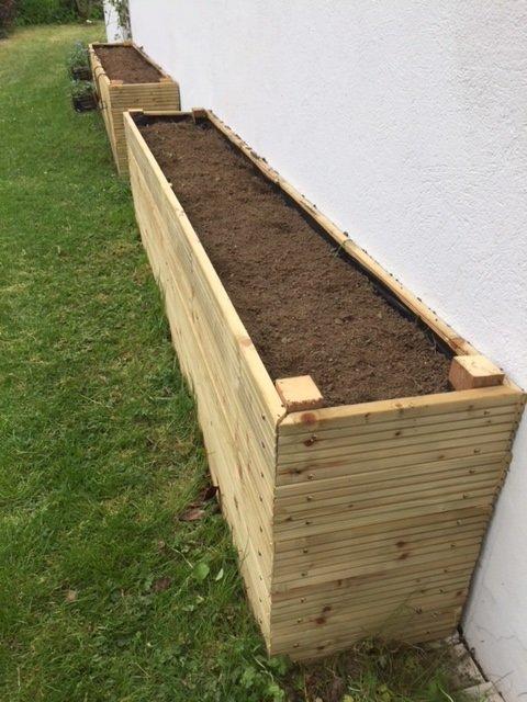 big wooden boxes filled with soil